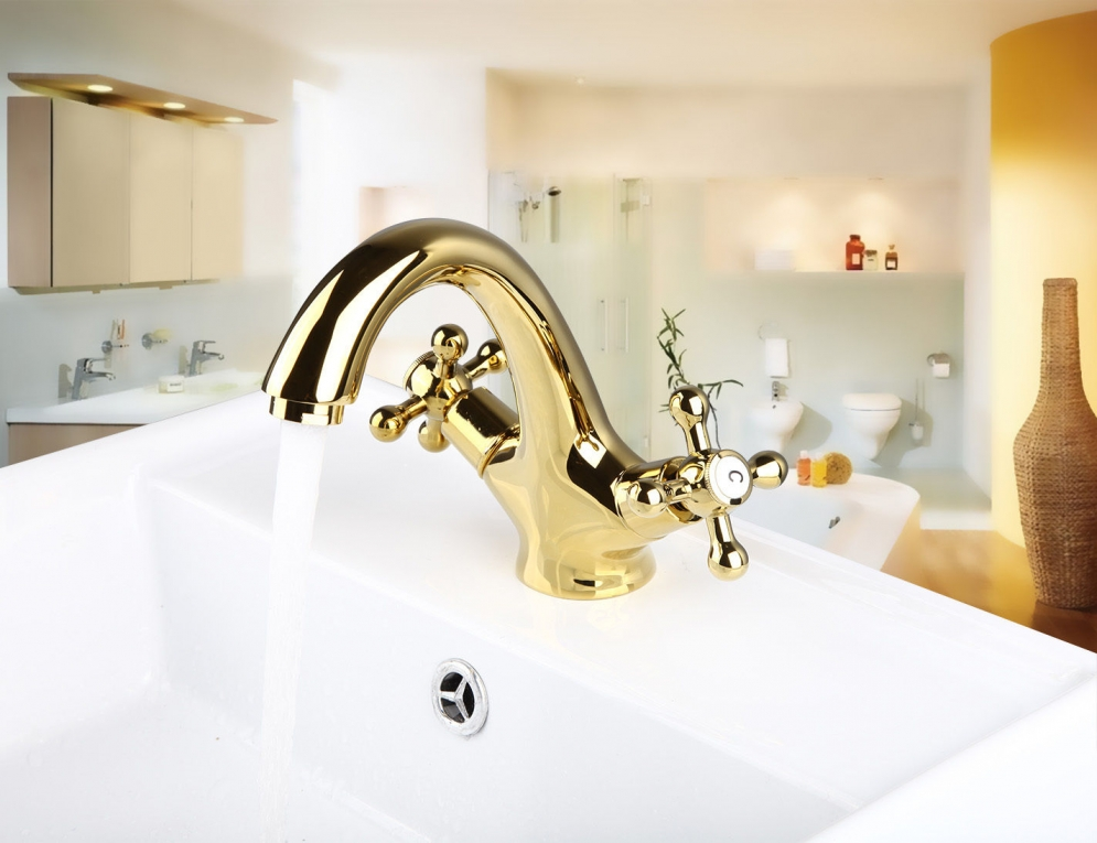 Elegante gouden wastafelkraan met witte elementen afgewerkt goud